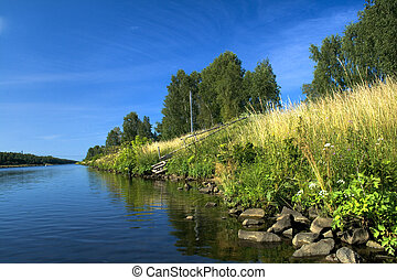 River bank against deep blue sky