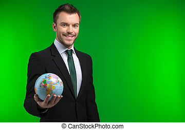 Young businessman keeps world in his hand Smiling man...