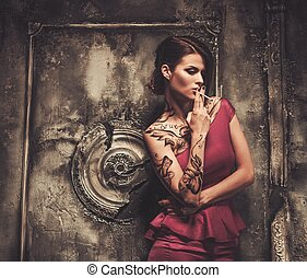 Smoking tattooed beautiful woman in old spooky interior