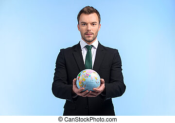 Young businessman keeps world in his hands Business man...