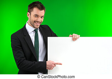 Happy smiling business man showing blank signboard. Young...