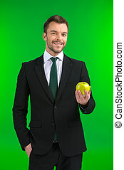 Businessman holding green apple in his hand young guy...