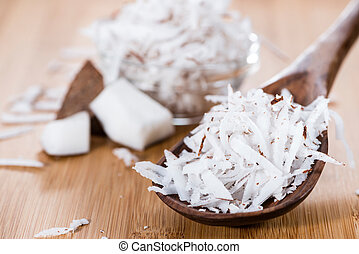 Grated Coconut (detailed close-up shot) on wooden background