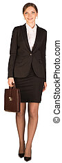 Isolated young business woman walking with briefcase