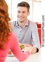 back of woman holding biyfriend's hand at restaurant. man's and woman's hands on table in cafe