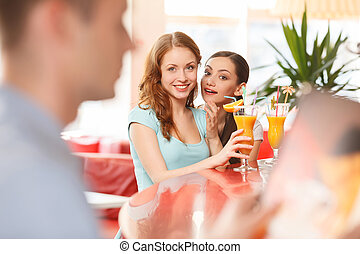 Two women whispering and smiling in cafe. redhead girl looking at boy at next table
