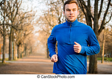Man jogging in early spring nature - Young man jogging in...