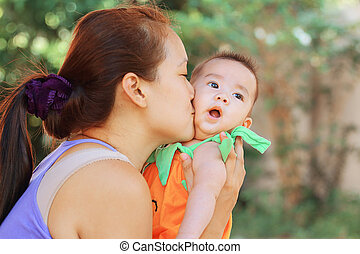 baby - Mother kissing her baby