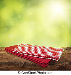 Empty wooden table with red napkins over green background