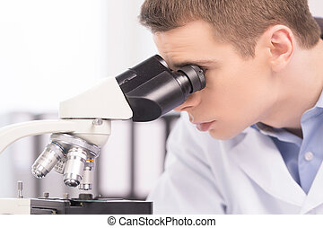 young man studying chemical elements in laboratory close-up...