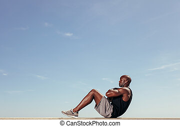 Fitness model doing crunches - Side view of fitness model...