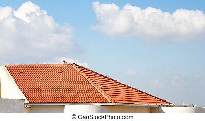 Orange tiled roof under the cloudy blue sky