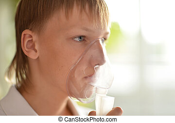 Ill boy with inhalator over natural background