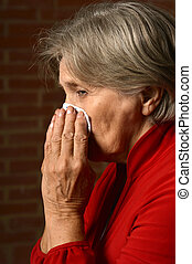 Sick elder woman in red on a background of a brick