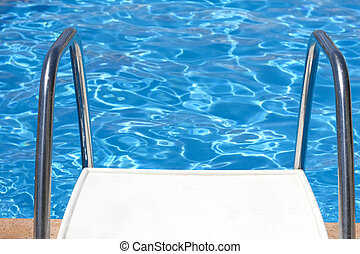 Stairs to swimming pool with blue water in background