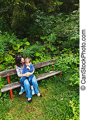 Mother and son sitting on park bench