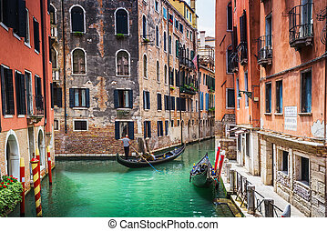 Tourists travel on gondolas at canal - VENICE, ITALY - JUNE...