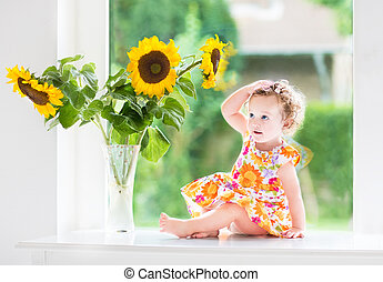 Baby girl with sunflowers - Beautiful curly baby girl...