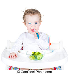 Portrait of a cute toddler eating broccoli in a white high...