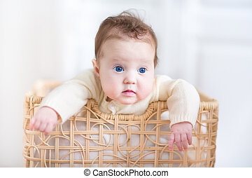 Adorable baby girl with beautiful blue eyes playing in a laundry