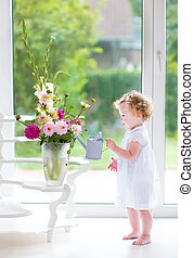 Adorable baby girl watering flowers - Adorable curly baby...