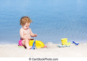 Funny baby girl playing on a beautiful beach with clear blue wat