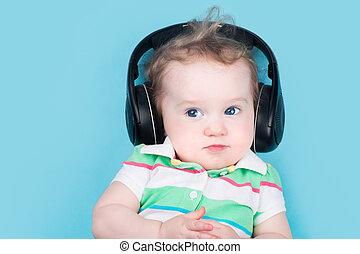 Funny little baby on a blue background wearing huge black earpho