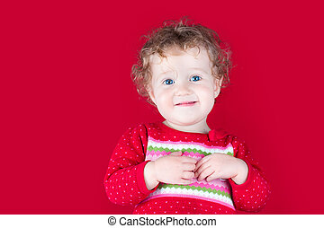 Happy smiling baby girl wearing a red Christmas jacket on...