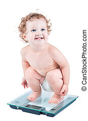 Happy laughing baby watching her weight on a scale, isolated...