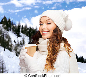 woman in hat with takeaway tea or coffee cup - winter...