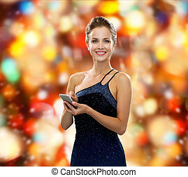smiling woman in evening dress with smartphone - technology,...