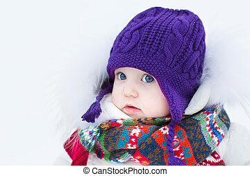 Cute baby girl wearing a warm winter hat and a colorful...