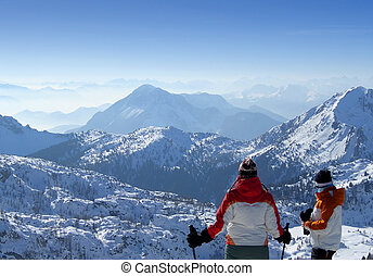 Two skiers looking over mountains top