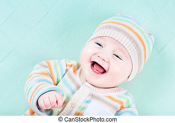 Adorable laughing baby wearing a warm knited jacket and hat...