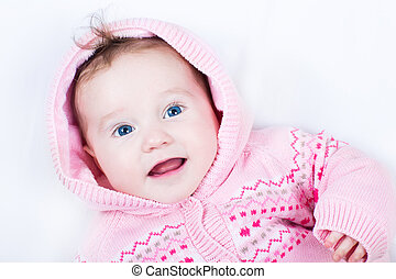 Happy smiling baby girl wearing a warm knitted jacket with...