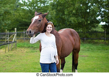 Attractive young pregnant woman and a horse standing in a...