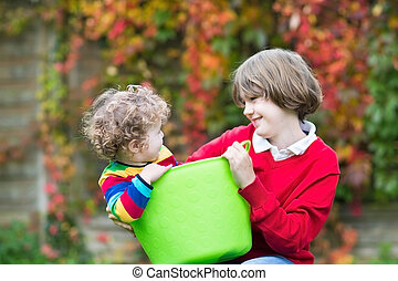 Laughing boy playing with his little baby sister in a laudry bas