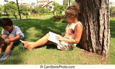 family leisure time in the park - mother reading book and...