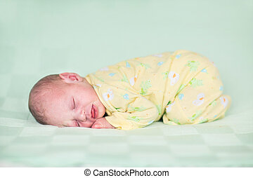 Sweet newborn baby sleeping on a green knitted blanket