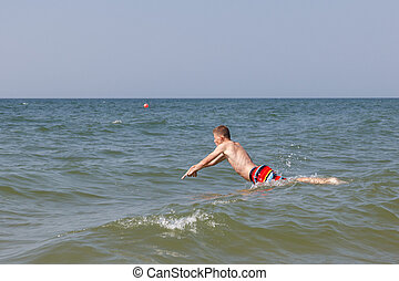 Jumping in water - A teen boy juming into water to swim