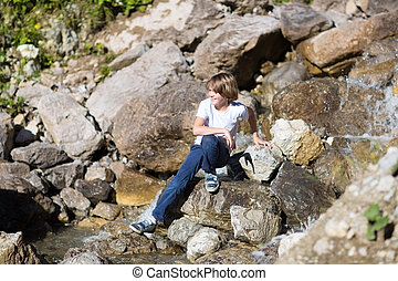 Smiling happy teenage boy crossing a small river in the mountain