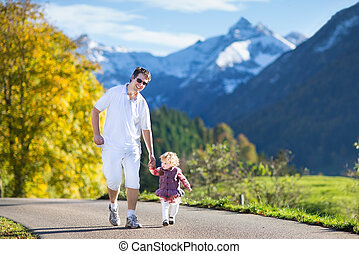 Young active father running with his baby daughter on a road bet