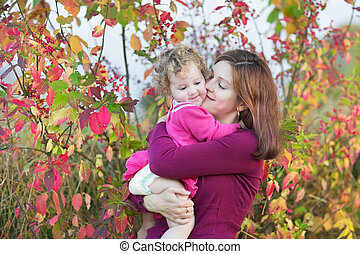 Happy young mother kissing her litte toddler daughter in a...