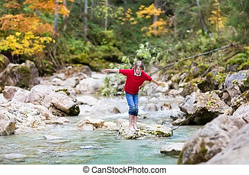 Smiling happy boy trying to cross a wild mountain river...