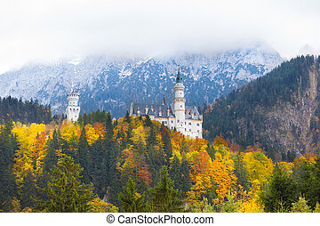 Neuschwanstein castle in Germany in autumn with clouds...
