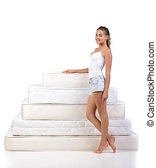 Woman and mattress - Portrait of a woman standing near a lot...