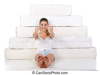 Woman and mattress - Portrait of a woman sitting near many...