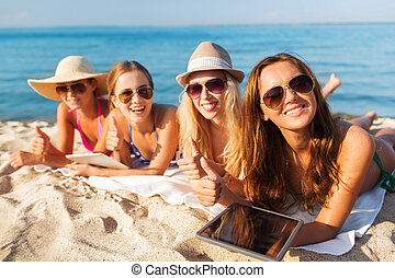 group of smiling young women with tablets on beach - summer...