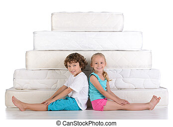 Children and many mattresses - Young children sitting on...