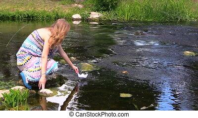 girl run paper boat river - beatiful woman run small paper...